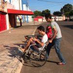 Estudante ajuda colega em cadeira de rodas a subir uma calçada